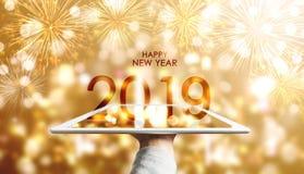 Guten Rutsch ins Neue Jahr 2019, Hand, die digitale Tablette mit Luxus- Gold-Bokeh-Feuerwerkshintergrund hält stockbild