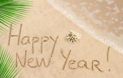 Guten Rutsch ins Neue Jahr handgeschrieben auf einem Sand Lizenzfreies Stockfoto