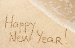 Guten Rutsch ins Neue Jahr handgeschrieben auf Sand Lizenzfreie Stockfotos