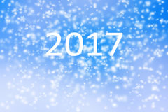 Guten Rutsch ins Neue Jahr-Hintergrund 2017 des unscharfen Schneesturms auf blauem Himmel Stockfotografie