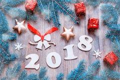 Guten Rutsch ins Neue Jahr-2018 Hintergrund mit 2017 Zahlen, Weihnachten spielt, blaue Tannenbaumaste Stillleben 2018 des neuen J Lizenzfreie Stockfotos