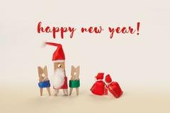 Guten Rutsch ins Neue Jahr-Kartenkonzept mit Wäscheklammercharaktere Santa Claus-Kindern und -geschenken Weichzeichnung, Stockfoto