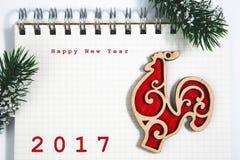 Guten Rutsch ins Neue Jahr-Konzept, Notizbuch mit hölzernem rotem Hahn Lizenzfreie Stockfotos