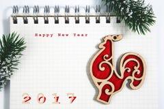 Guten Rutsch ins Neue Jahr-Konzept, Notizbuch mit hölzernem rotem Hahn Stockfoto