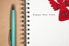 Guten Rutsch ins Neue Jahr-Konzept, Notizbuch und grüner Stift mit hölzernem Rot a Stockbild