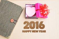 Guten Rutsch ins Neue Jahr 2016 mit Buch und Geschenk auf Weinlesebraunhintergrund Lizenzfreie Stockfotos