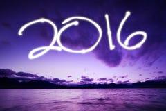 Guten Rutsch ins Neue Jahr mit dem Glühen nummeriert 2016 am Strand Lizenzfreie Stockbilder