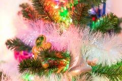 Guten Rutsch ins Neue Jahr mit immergrünem Baum, Spielwaren, Ingwerbrotmann und bunter Beleuchtung Stockfotos