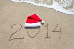 Guten Rutsch ins Neue Jahr 2014 mit Sankt-Hut auf Seestrandsand mit Welle Stockbild