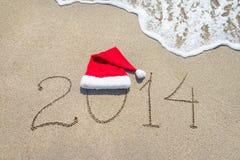 Guten Rutsch ins Neue Jahr 2014 mit Sankt-Hut auf Seestrandsand mit Welle Stockfoto