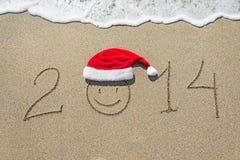 Guten Rutsch ins Neue Jahr 2014 mit smileygesicht im Weihnachtshut auf sandigem b Stockbilder