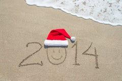 Guten Rutsch ins Neue Jahr 2014 mit smileygesicht in Sankt-Hut auf sandigem Strand Lizenzfreie Stockbilder