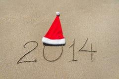 Guten Rutsch ins Neue Jahr 2014 mit Weihnachtshut auf sandigem Strandurlaub Lizenzfreie Stockfotografie