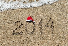 Guten Rutsch ins Neue Jahr 2014 mit Weihnachtshut auf sandigem Strandurlaub Stockfoto