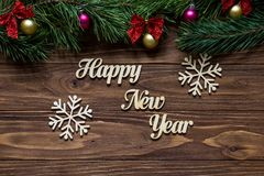 Guten Rutsch ins Neue Jahr mit zwei schönen Schneeflocken auf der Mitte des hölzernen Hintergrundes mit Kieferniederlassungen auf Stockbilder
