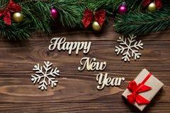 Guten Rutsch ins Neue Jahr mit zwei schönen Schneeflocken und einer Geschenkbox auf der Mitte des hölzernen Hintergrundes mit Kie Lizenzfreie Stockbilder