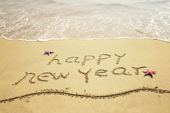 Guten Rutsch ins Neue Jahr-Mitteilung auf Sand Lizenzfreie Stockfotos
