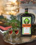 Guten Rutsch ins Neue Jahr- oder Weihnachtshintergrund mit Jagermeister-Alkoholgetränk, Elixier Flasche von Jagermeister mit Gläs lizenzfreie stockbilder