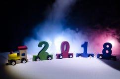 2018 guten Rutsch ins Neue Jahr, tragende Zahlen des hölzernen Spielzeugzugs von 2018-jährigem auf Schnee Spielzeugzug mit 2018 K Lizenzfreies Stockbild