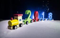 2018 guten Rutsch ins Neue Jahr, tragende Zahlen des hölzernen Spielzeugzugs von 2018-jährigem auf Schnee Spielzeugzug mit 2018 K Lizenzfreie Stockfotografie