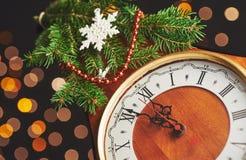 Guten Rutsch ins Neue Jahr um Mitternacht 2018, alte hölzerne Uhr mit Lichterkette und Tannenzweige Stockfotografie