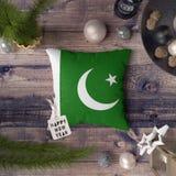 Guten Rutsch ins Neue Jahr-Umbau mit Pakistan-Flagge auf Kissen Weihnachtsdekorationskonzept auf Holztisch mit reizenden Gegenst? lizenzfreie stockfotos