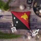 Guten Rutsch ins Neue Jahr-Umbau mit Papua-Neu-Guinea Flagge auf Kissen Weihnachtsdekorationskonzept auf Holztisch mit reizenden  stockbild