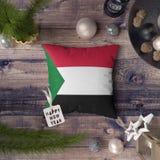 Guten Rutsch ins Neue Jahr-Umbau mit Sudan-Flagge auf Kissen Weihnachtsdekorationskonzept auf Holztisch mit reizenden Gegenst?nde lizenzfreie stockbilder