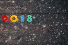 Guten Rutsch ins Neue Jahr 2018 von wirklichen hölzernen Zahlen auf dunklem hölzernem Hintergrund mit Schnee Lizenzfreie Stockbilder