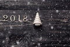 Guten Rutsch ins Neue Jahr 2018 von wirklichen hölzernen Zahlen mit einem Tannenbaum auf dunklem hölzernem Hintergrund mit Schnee Stockfotografie