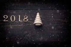 Guten Rutsch ins Neue Jahr 2018 von wirklichen hölzernen Zahlen mit einem Tannenbaum auf dunklem hölzernem Hintergrund mit Schnee Stockbilder