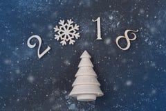 Guten Rutsch ins Neue Jahr 2018 von wirklichen hölzernen Zahlen mit einem Tannenbaum auf schwarzem Hintergrund mit Schnee Stockfotografie
