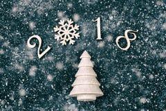 Guten Rutsch ins Neue Jahr 2018 von wirklichen hölzernen Zahlen mit einem Tannenbaum auf schwarzem Hintergrund mit Schnee Lizenzfreie Stockfotografie