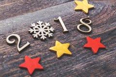 Guten Rutsch ins Neue Jahr 2018 von wirklichen hölzernen Zahlen mit Schneeflocke und Sternen auf hölzernem Hintergrund Selektiver Lizenzfreies Stockfoto