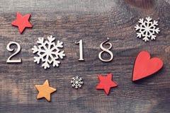 Guten Rutsch ins Neue Jahr 2018 von wirklichen hölzernen Zahlen mit Schneeflocken und Sternen auf hölzernem Hintergrund Stockbild