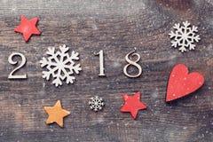 Guten Rutsch ins Neue Jahr 2018 von wirklichen hölzernen Zahlen mit Schneeflocken und Sternen auf hölzernem Hintergrund mit Schne Stockbilder