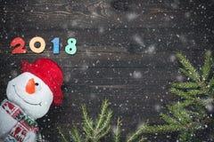 Guten Rutsch ins Neue Jahr 2018 von wirklichen hölzernen Zahlen mit Schneemann- und Tannenbaumasten mit Schnee auf dunklem hölzer Lizenzfreies Stockbild