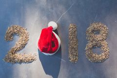 2018-guten Rutsch ins Neue Jahr-Zahlen mit Reis- und Santa Claus-Rothut Lizenzfreies Stockfoto