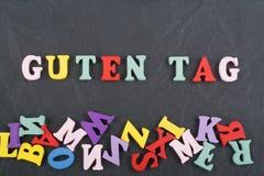GUTEN-UMBAU-Wort auf dem schwarzen Bretthintergrund verfasst von den hölzernen Buchstaben des bunten ABC-Alphabetblockes, Kopienr lizenzfreies stockfoto