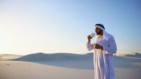 Gutenmorgen für männlichen Scheich in der Mitte der enormen Wüste über Tasse Kaffee gegen blauen Himmel und Dünen im Freilicht stock footage