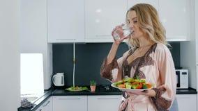 Gutenmorgen, hält glückliche Frau im silk Nachthemd Teller mit Gemüsesalat und trinkt Wasser vom Glas stock video
