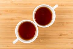 Gutenmorgen, schossen zwei weiße Tassen Tee lokalisiert auf einem hölzernen Hintergrund von oben, Frühstück lizenzfreies stockbild