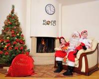 Guter Geist des neuen Jahres: Baum, große Geschenktasche, Kamin und decorati stockfotos