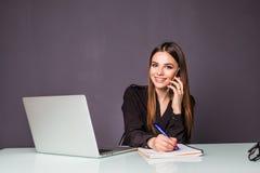 Gutes Geschäftsgespräch Nette junge Schönheit in den Gläsern sprechend am Handy und Laptop mit Lächeln beim Sitzen an verwendend Lizenzfreie Stockfotografie