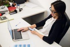 Gutes Geschäftsgespräch Nette junge Schönheit in den Gläsern sprechend am Handy und Laptop mit Lächeln verwendend während Stockbilder