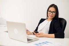 Gutes Geschäftsgespräch Nette junge Schönheit in den Gläsern sprechend am Handy und Laptop mit Lächeln verwendend während Lizenzfreie Stockfotos