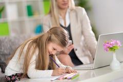 Gutes Mädchenspiel während Mutterarbeit Lizenzfreie Stockfotografie