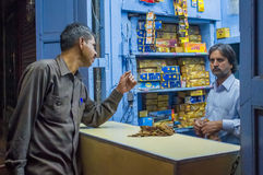 Gutka shop. JODHPUR, INDIA - 16 FEBRUARY 2015: Indian vendor sells gutka to customer. Gutka has mild stimulant effect and is consumed by sucking and chewing Stock Images
