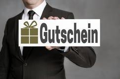 Gutschein in Duitse Giftkaart wordt gehouden door een zakenman stock foto's