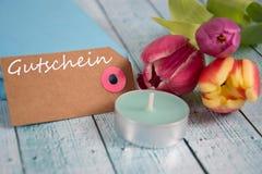 Gutschein - the german word for coupon. Gutschein inscription written on paper tag Stock Image